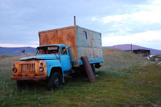 Abandoned broken mud hut at arctic summer tundra