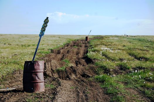 Old oil drum with road mark stake at tundra