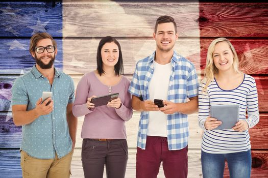Portrait of smiling business people using electronic gadgets  against composite image of usa national flag