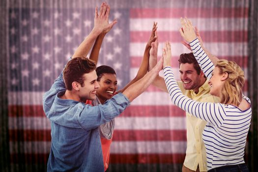 Happy creative team giving high fives to each other against composite image of usa national flag