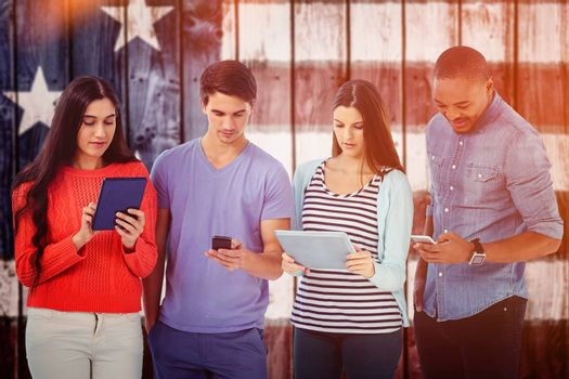 Young creative team looking at phones and tablets against composite image of usa national flag