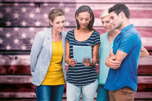 Group portrait of happy colleagues using tablet against composite image of usa national flag