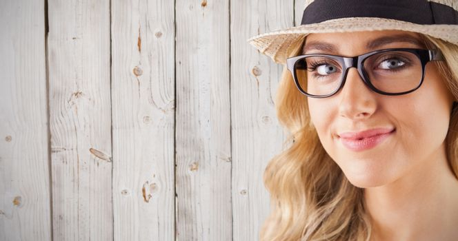 Gorgeous blonde hipster smiling against wooden background