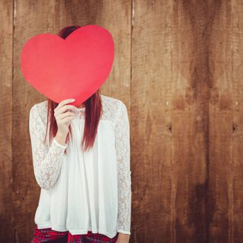 Smiling hipster woman behind a big red heart against weathered oak floor boards background