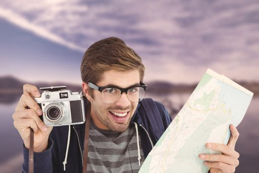 Portrait of happy man holding map and camera against lake