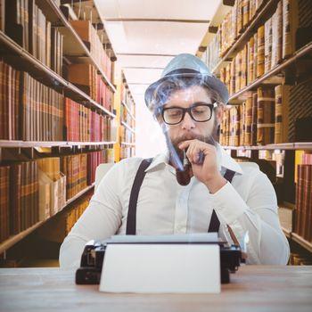 Hipster smoking pipe while sitting looking at typewriter against close up of a bookshelf
