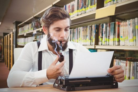Hipster with smoking pipe working on typewriter against rows of bookshelves in the library