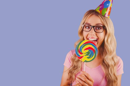 A beautiful hipster holding a giant lollipop  against purple