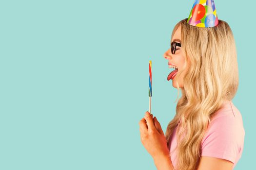 Side view of a beautiful hipster holding a giant lollipop  against blue background