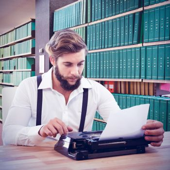 Hipster using typewriter at desk in office against close up of a bookshelf