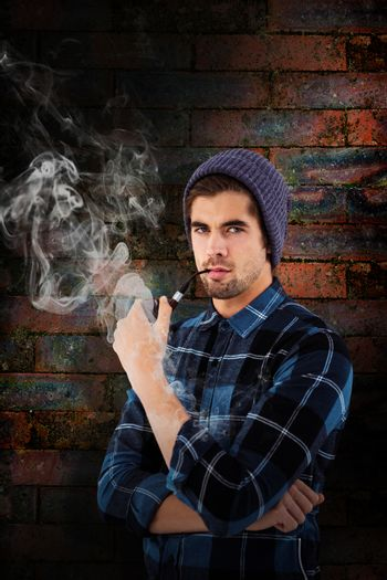 Portrait of hipster holding smoking pipe against texture of bricks wall