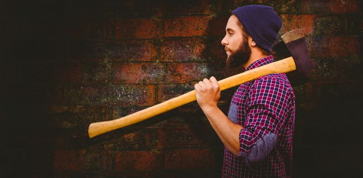 Side view of hipster with axe on shoulder against texture of bricks wall