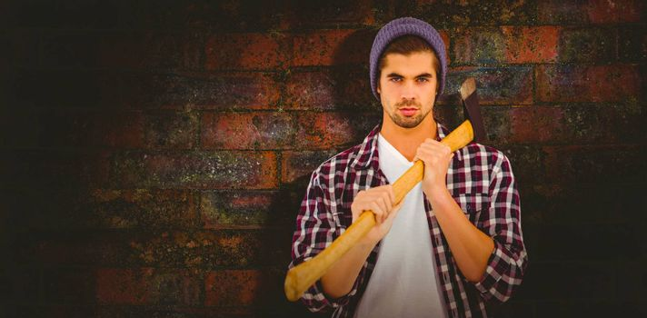 Portrait of confident man holding axe on shoulder against texture of bricks wall