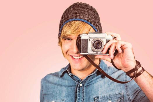 Smiling hipster man taking picture against pastel pink
