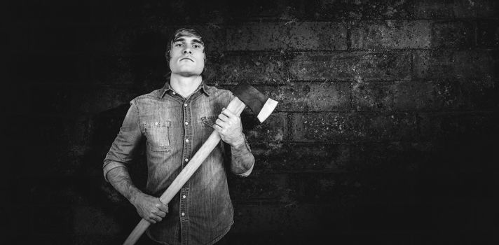 Front view of hipster standing with axe against texture of bricks wall