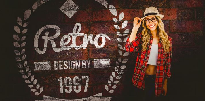 Gorgeous smiling blonde hipster posing against texture of bricks wall