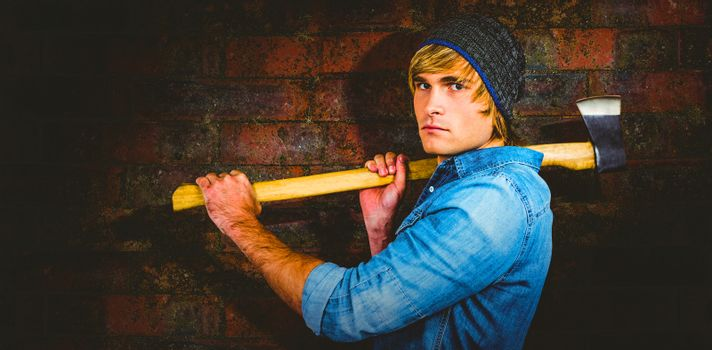 Profile of hipster standing with axe against texture of bricks wall