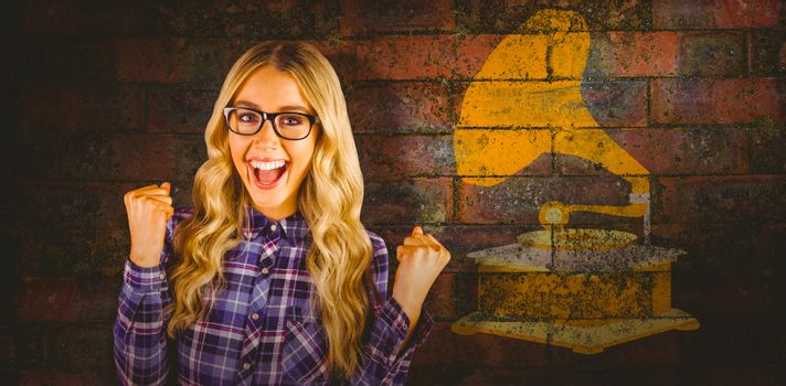 Gorgeous blonde hipster celebrating success against texture of bricks wall