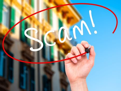 Man Hand writing  Scam! with black marker on visual screen. Isolated on nature. Business, technology, internet concept. Stock Image