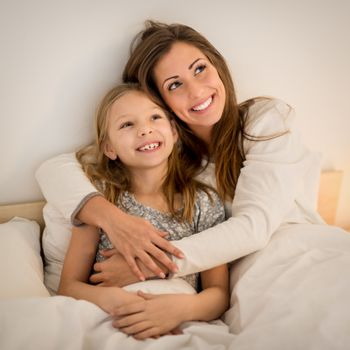 Beautiful smiling mother and her daughter hugging in bed. They are sitting on bed at pajamas and smiling.