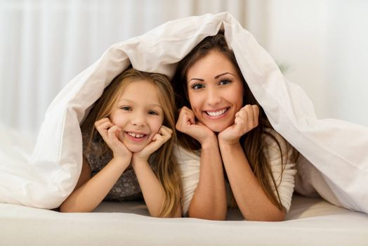 Beautiful smiling mother and her daughter having fun in bed. They lie in bed looking at camera and peeking under the blanket with smile.