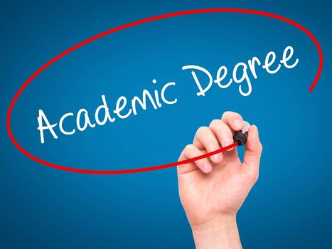Man Hand writing Academic Degree with black marker on visual screen. Isolated on blue. Business, technology, internet concept. Stock Photo