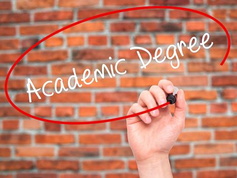 Man Hand writing Academic Degree with black marker on visual screen. Isolated on bricks. Business, technology, internet concept. Stock Photo