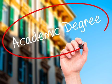 Man Hand writing Academic Degree with black marker on visual screen. Isolated on city. Business, technology, internet concept. Stock Photo
