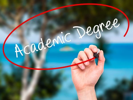 Man Hand writing Academic Degree with black marker on visual screen. Isolated on nature. Business, technology, internet concept. Stock Photo