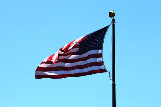 USA flag with a blue sky in the background.