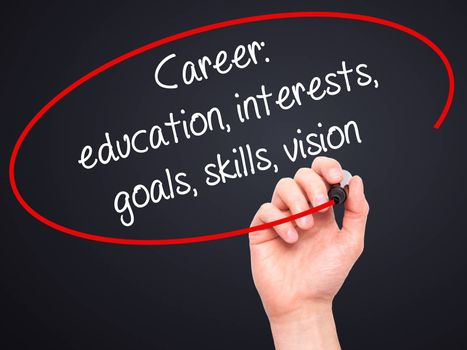 Man Hand writing Career: education, interests, goals, skills, vision with black marker on visual screen. Isolated on black. Business, technology, internet concept.