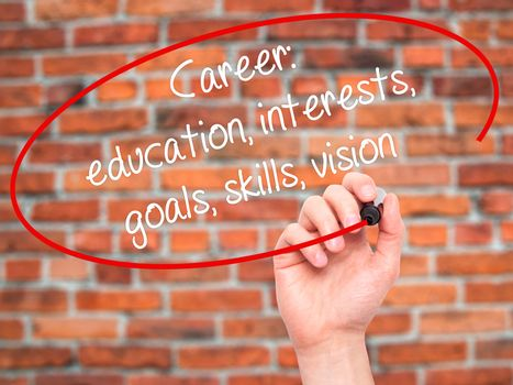 Man Hand writing Career: education, interests, goals, skills, vision with black marker on visual screen. Isolated on bricks. Business, technology, internet concept.