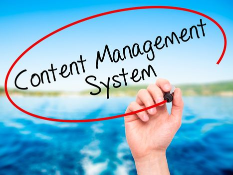 Man Hand writing Content Management System  with black marker on visual screen. Isolated on nature. Business, technology, internet concept. Stock Photo
