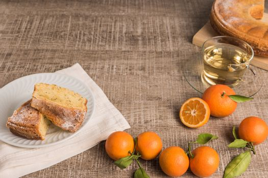 Slices of clementine cake with powdered sugar topping and cup of