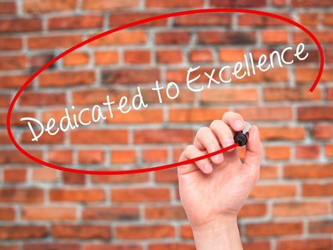 Man Hand writing Dedicated to Excellence  with black marker on visual screen. Isolated on bricks. Business, technology, internet concept.
