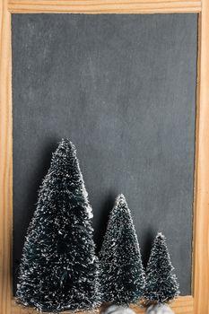 Blank rustic Christmas chalkboard slate with christmas trees