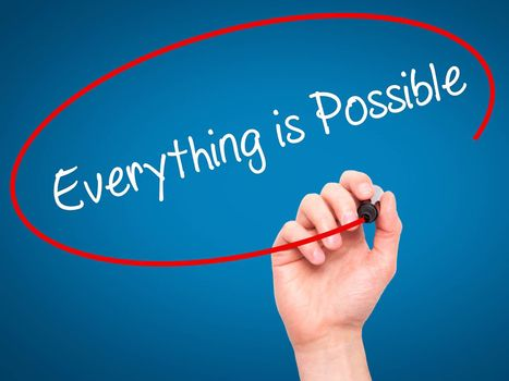 Man Hand writing Everything is Possible with black marker on visual screen. Isolated on blue. Business, technology, internet concept. Stock Photo