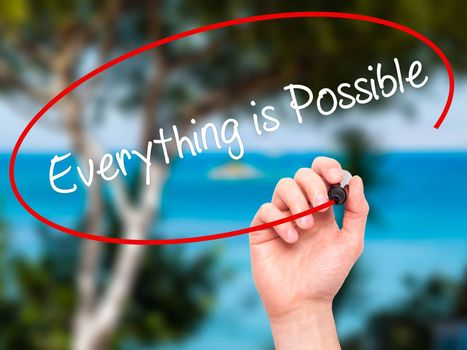 Man Hand writing Everything is Possible with black marker on visual screen. Isolated on nature. Business, technology, internet concept. Stock Photo