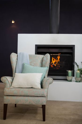 Armchair next to fireplace