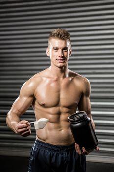 Shirtless man holding protein powder