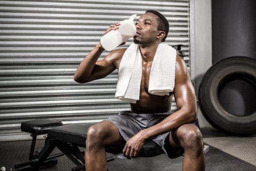Shirtless man drinking protein shake