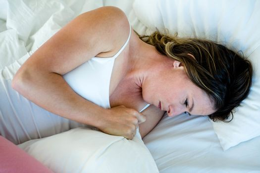 sick woman lying in bed looking unwell