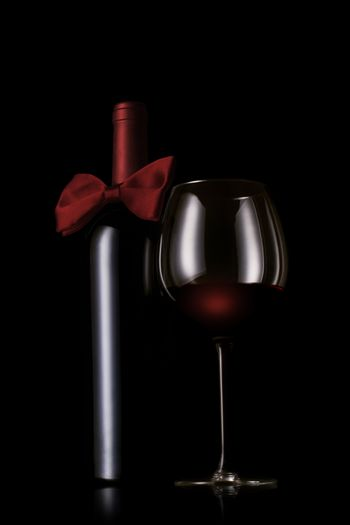 A red wine bottle with bow tie next to a wine glass on black background