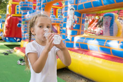 Anapa, Russia - September 16, 2015: Four-year girl drinks water from a bottle in the background a childrens playground with inflatable trampolines