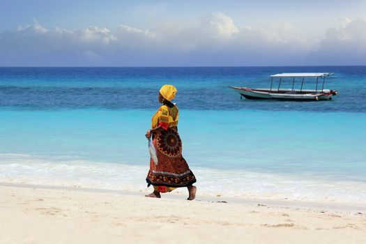 Zanzibar, Tanzania - January 7, 2016: An African woman in traditional dress with fish walks down the beach. Zanzibar, Tanzania