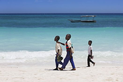 Zanzibar, Tanzania - January 6, 2016: Three unknown African boy walking on the beach in Zanzibar