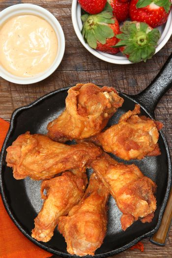 Chicken Wings in Skillet with Strawberries and Sauce