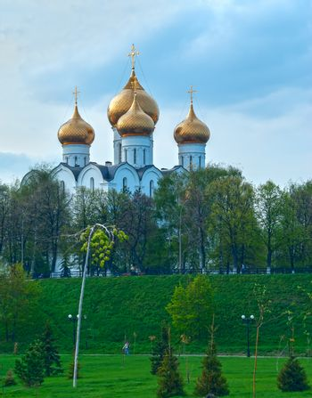 Ancient ortodox christian curch with golden domes in cloudy day