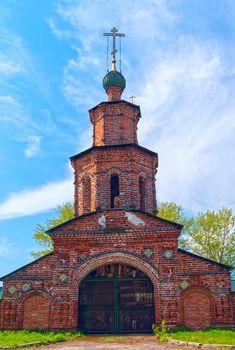 Repairing church of red brick near Yaroslavl in summer sunny day