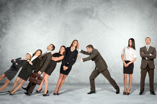 Businessman supporting falling people on wall background, co-working concept